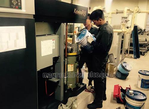 Nhân viên đang thay dầu có máy nén khí trục vít
